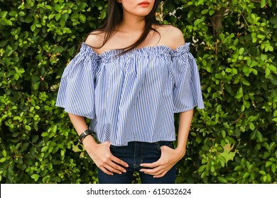 Close-up Off the Shoulder blue shirt and blue jeans on trees background