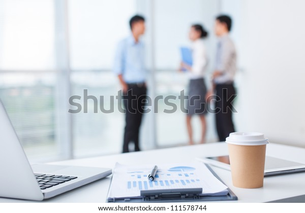 Close-up of office desk with business team behind