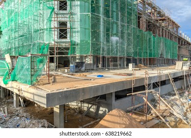 Close-up office and residential building under construction with safety net, green grid prevent object falling from height in Malacca, Malaysia. Scaffolding, formwork in installation, building fencing
