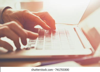 A closeup of an office worker using a computer keyboard, laptop on a sunny morning, evening.