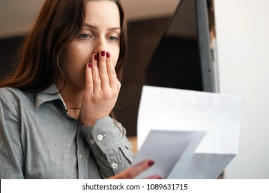 Close-up of an office worker. Woman reading negative news in letter. Shocked beauty girl business manager received layoff message letter from company feeling surprised. An agitated girl without joy.