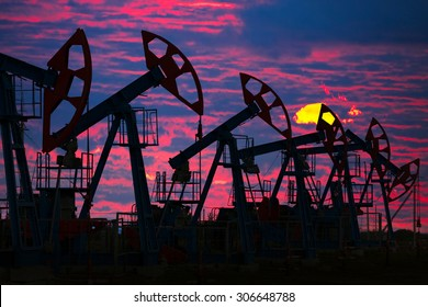 close-up of oil pumps on background of dramatic clouds at sunset