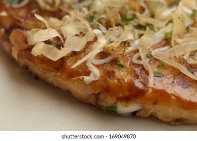 Close-up of Okonomiyaki (Japanese savoury pancake containing a variety of ingredients)