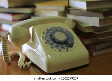 Close-up of old antique telephone in library book stack is the background selective focus and shallow depth of field