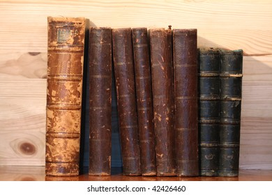 Closeup of old books standing in row on wooden background
