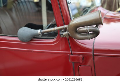 Closeup of an old brass hooter or a horn of vintage red car.