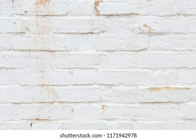 Closeup of old brick wall painted white and distressed, peeling and stained. Ideal for grunge background texture