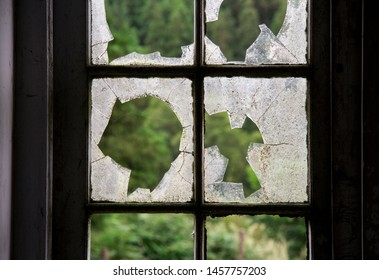 Close-up of old broken window glass in frame, abandoned house