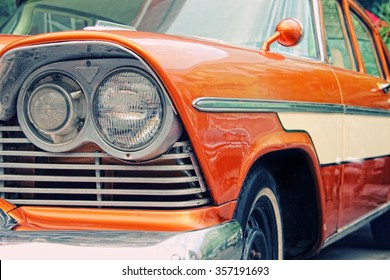 Closeup of old car with orange colored paint on automobile show