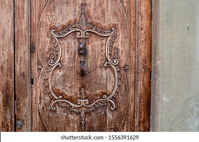 Close-up of an old carved wood door with a vintage pattern and a knocker in wrought iron, Italy