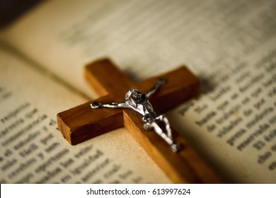 closeup of an old christian crucifix on an open bible, with a retro filter effect