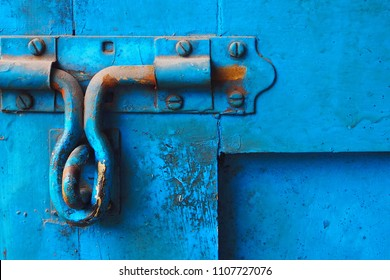 Closeup of the old and classic rusty door latch and lock on wooden blue painted door. Vintage decoration and lifestyle concept