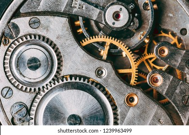Close-Up Of Old Clock Watch Mechanism. Retro Clockwork Watch With Gray And Golden Gearwheels Gears. Vintage Movement Mechanics
