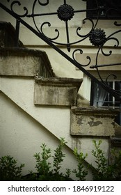 Closeup of old concrete stairs outside a historical building with decorative metal railings and corner of window in the background