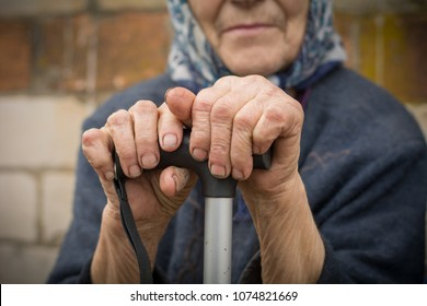 close-up of old dirty wrinkled woman hands holding walking stick. Senior people health care