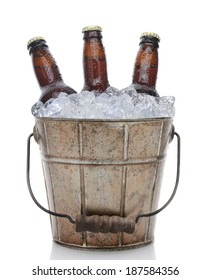 Closeup of an old fashioned beer bucket with three brown bottles of cold beer. Isolated on white with reflection.