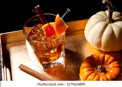 Closeup of Old Fashioned Cocktail at a bar ready to be served. Mini pumpkins and cinnamon sticks. Fall Drinks series.