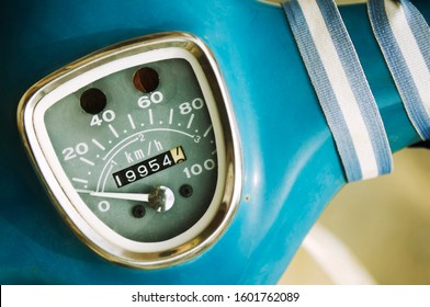 Close-up of old fashioned speedometer odometer on classic blue European style scooter