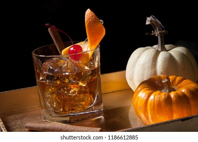 Closeup of Old Fashioned Whiskey Cocktail at a bar ready to be served. Mini pumpkins and cinnamon sticks. Fall Drinks series.