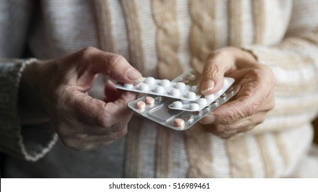 closeup of old female hands holding packaged pills