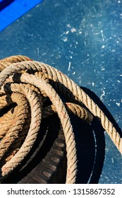 Close-up the old frayed boat rope on blue texture background.