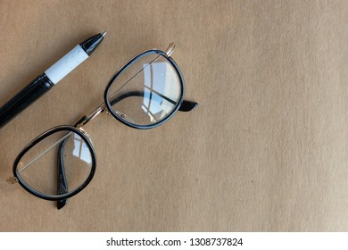 closeup old glasses and pen on open book on table with soft-focus and over light in the background