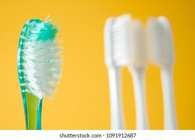 Close-up old green plastic toothbrush with three white toothbrushes behind on yellow background