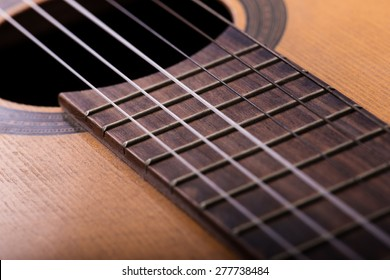 Closeup of old guitar body with sound hole and strings