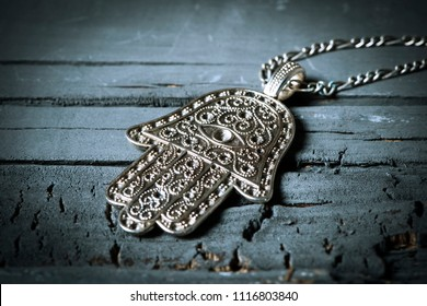 closeup of an old hamsa amulet, also known of the hand of fatima or the hand of mary, on a gray rustic wooden surface