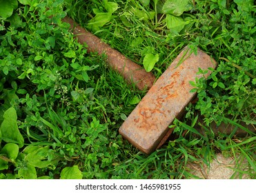 Close-up old heavy iron sledgehammer with a metal handle on green grass background. Conceptual background about the lost Thor's hammer Mjolnir and dead heroes. Top view
