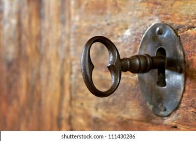 Closeup van een oud sleutelgat met sleutel op een houten antieke deur