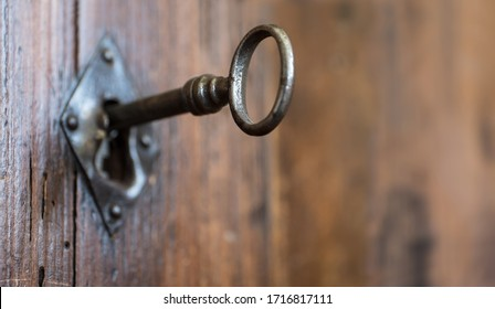 Close-up of an old keyhole with key on a wooden antique door. Narrow depth of field. Space for text at the right side
