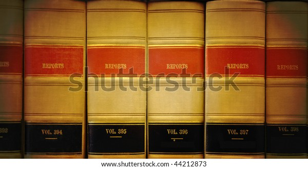 A closeup of old looking law books in a library on a shelf. The lighting is on the center. Colors are brown, red and black.