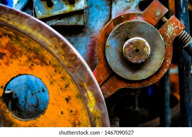 closeup old machine with flywheel.  Focus on the round washer