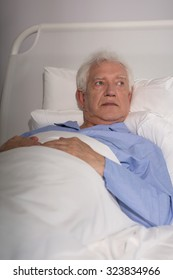 Close-up of an old man lying in hospital bed