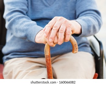 Closeup of an old man's hand holding his stick.
