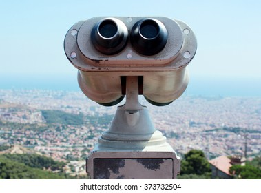 close-up old metal binoculars through which you can observe a European city