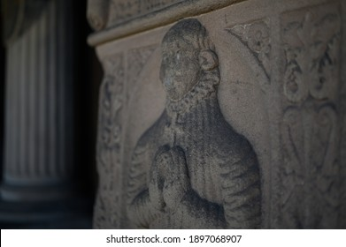 Closeup of old relief sculpture of a man holding cross and praying. Ancient sandstone tombstone with christian ornaments and collumn in the background.