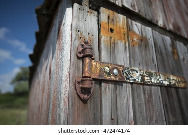 Closeup of an old rusty hinge on a boathouse