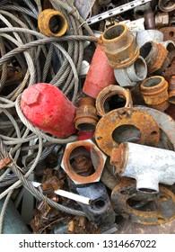 Closeup of old rusty motor and plumbing parts in container at scrap yard.