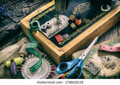 Closeup of an old sewing machine and accessories for sewing, scissors, needles and a tailor tape on a table. The concept of sewing accessories. Retro toning