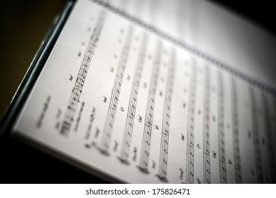 Closeup of old sheet music in dark background