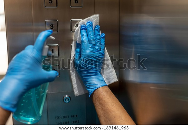 Closeup of old staff hand using wet wipe cleaning an elevator push button control panel with a blue sanitizer bottle.Disinfection,cleanliness and healthcare,Anti Corona virus,COVID-19.Selective focus.