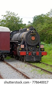 Close-up of old steam locomotive view from front with rails in the foreground