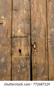 Close-up of old, textured, rustic, weathered, brown wooden door.