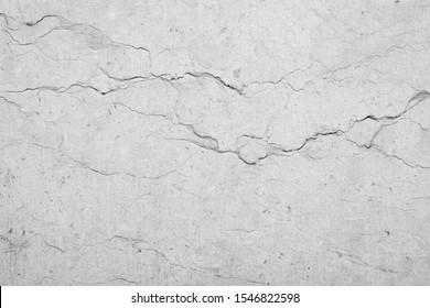 Close-up of an old, weathered and cracked stone wall with veins. High resolution full frame textured background in black and white.