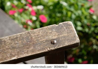 Close-up of Old Weathered Rocking Chair Arm with Flowers in Background