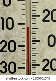 Closeup of an old weathered, worn, dirty red mercury thermometer reading eleven degrees Fahrenheit and minus twelve Celsius