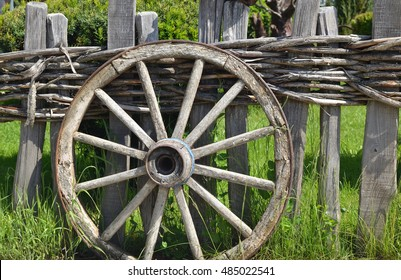 Closeup of an old wheel of a traditional cart leaning on a wooden fence