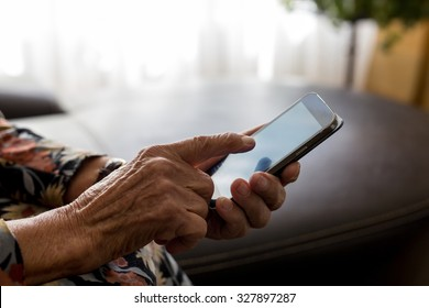 Closeup of old woman hands holding mobile phone